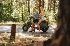 Homme barbu sur le scooter avec l'amie heureuse dehors Photos stock