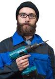 Homme barbu tenant dans une main le foret électrique Photographie stock
