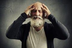 Homme barbu tenant sa tête et grimaçant en douleur Image libre de droits