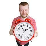 Homme barbu tenant un réveil rouge photographie stock libre de droits
