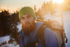 Homme barbu trimardant en montagne d'hiver au coucher du soleil photos libres de droits
