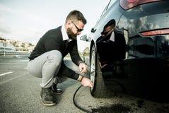 Homme barbu vérifiant la pression des pneus images stock