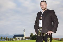Homme bavarois de tradition avec une église à l'arrière-plan photographie stock