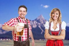 Homme bavarois heureux avec la tasse de bière et la femme blonde avec du ce de dirndl photo libre de droits