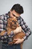 Homme beau de hippie de portrait de plan rapproché le jeune, embrassant son chien rouge de bon ami a isolé le fond clair Émotions Images stock