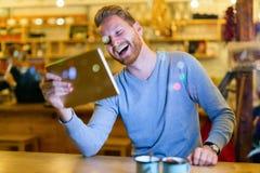 Homme bel à l'aide du comprimé numérique dans le café Images stock