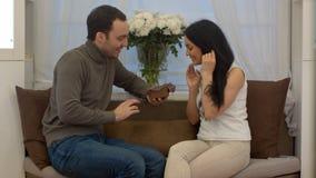 Homme bel étonnant son amie avec un cadeau à la maison dans le salon photo libre de droits
