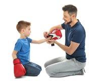 Homme bel aidant son fils à mettre dessus des gants de boxe, sur le fond blanc Image libre de droits