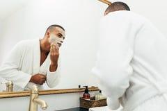 Homme bel appliquant un masque facial d'argile naturel photographie stock
