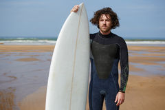 homme bel aux cheveux bouclés se tenant sur la plage et regardant pour vos amis Image stock