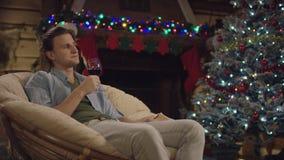 Homme bel aux cheveux longs s'asseyant avec un verre de vin dans la nuit de Noël par l'arbre décoré banque de vidéos