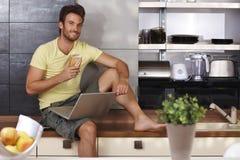 Homme bel avec l'ordinateur portable dans la cuisine image libre de droits
