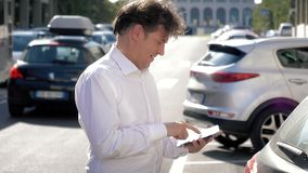 Homme bel avec la chemise blanche parlant au téléphone marchant avec le comprimé clips vidéos