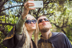 Homme bel avec la fille assez gaie de barbe et de jeunes avec des verres faisant le selfie Images stock