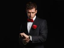 Homme bel avec la fleur attendant et regardant l'horloge homme de marié de jeunes dans le costume Photographie stock libre de droits
