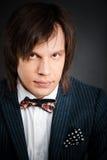 Homme bel avec la longue brune de cheveux et yeux bruns dans le costume foncé Photographie stock libre de droits
