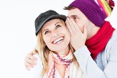 Homme bel avec le chapeau indiquant le secret à l'amie Images stock