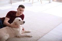 Homme bel avec le chien se trouvant sur le tapis Photographie stock libre de droits