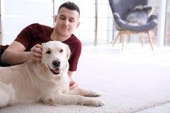 Homme bel avec le chien se trouvant sur le tapis Image stock