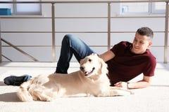 Homme bel avec le chien se trouvant sur le tapis Photo libre de droits