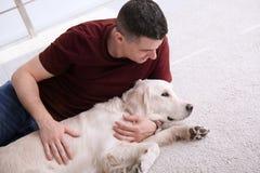 Homme bel avec le chien se trouvant sur le tapis Photos stock