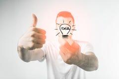 Homme bel avec les verres bleus tenant une carte de crédit sur le fond blanc Image stock