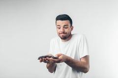 Homme bel avec les verres bleus tenant une carte de crédit sur le fond blanc Photographie stock