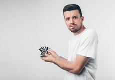 Homme bel avec les verres bleus tenant une carte de crédit sur le fond blanc Photos libres de droits