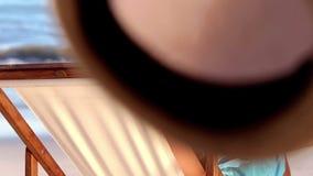 Homme bel avec un chapeau de paille détendant sur une chaise de plate-forme clips vidéos