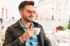 Homme bel ayant la pause-café dans des regards de ville à dégrossir image stock
