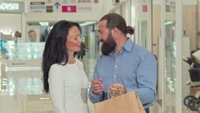 Homme bel barbu et sa belle épouse regardant à l'intérieur des sacs à provisions banque de vidéos