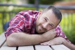 Homme bel barbu se trouvant sur un banc images stock