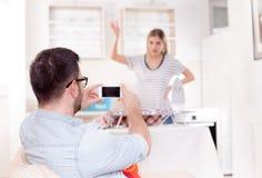 Homme bel capturant l'épouse tout en repassant Photo stock