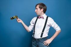 Homme bel choqué dans la chemise, bretelle, noeud papillon avec la main sur la hanche, tenant et regardant la couronne d'or photos libres de droits