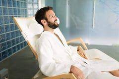 Homme bel détendant dans la chaise au centre de station thermale photographie stock libre de droits