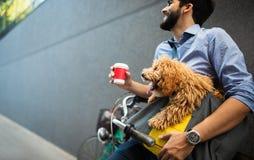 Homme bel d'affaires sur le caf? potable de rue avec le chien image stock