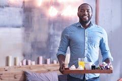 Homme bel d'Afro-américain tenant le plateau de petit déjeuner dans la chambre à coucher Image libre de droits