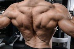 Homme bel d'instructeur de forme physique dans le muscle de gain de gymnase photos stock