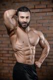 Homme bel d'instructeur de forme physique dans le muscle de gain de gymnase Photos libres de droits