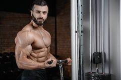 Homme bel d'instructeur de forme physique dans le muscle de gain de gymnase Photographie stock