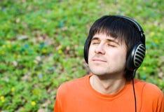 Homme bel dans des écouteurs extérieurs. Source image stock