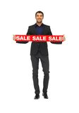 Homme bel dans le costume avec le signe de vente Image stock