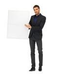 Homme bel dans le costume avec un conseil vide Image stock