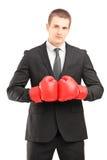 Homme bel dans le costume noir avec la pose rouge de gants de boxe Image stock