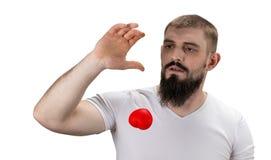 Homme bel dans le T-shirt blanc tenant le coeur rouge dans sa main Photos libres de droits