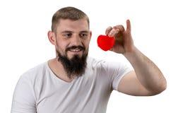 Homme bel dans le T-shirt blanc tenant le coeur rouge dans sa main Image libre de droits