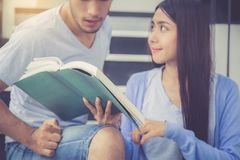 Homme bel de couples de plan rapproché et beau livre de lecture de femme et heureux asiatiques à la maison Image libre de droits