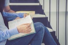 Homme bel de couples de plan rapproché et beau livre de lecture de femme et heureux asiatiques à la maison Photo libre de droits