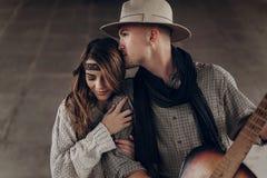 Homme bel de cowboy avec une guitare embrassant la belle femme indépendante Photos stock