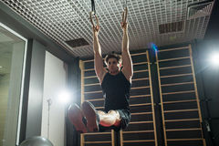 Homme bel de forme physique faisant l'exercice de plongement utilisant des anneaux dans le gymnase sport Photographie stock libre de droits